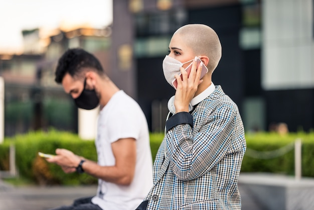 Donna che usa il suo cellulare durante la pandemia covid-19, concetti di distanza sociale, tecnologia e virus corona.