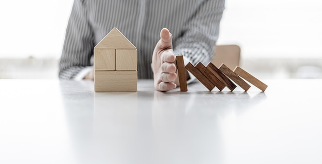 Donna che usa la mano per evitare che blocchi di legno cadano su blocchi di legno a forma di casa, assicurazione per prevenire i rischi che ci faranno risparmiare prezzi elevati, idee per l'assicurazione sulla casa.
