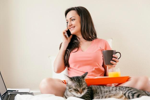 Donna che usa il cellulare e fa colazione. lei è in camera da letto