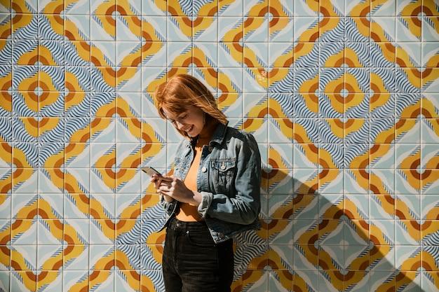 Donna che usa il telefono su un muro moderno