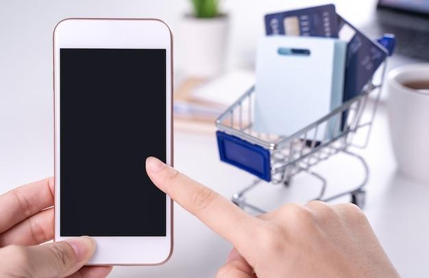 Donna che utilizza tenendo il telefono cellulare intelligente rimanendo a casa il pagamento elettronico online