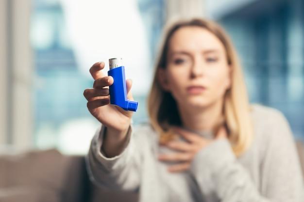 Donna che usa l'inalatore mentre soffre di asma a casa