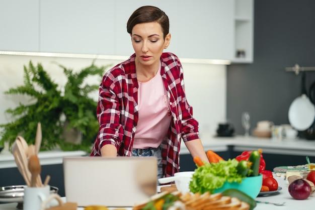Donna che utilizza computer portatile durante la cottura o la cottura tenendo le uova in una mano.