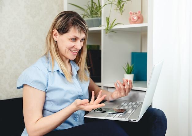 Donna che per mezzo del computer portatile per la video chiamata a casa. videoconferenza online