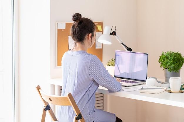 Donna che utilizza laptop, posto di lavoro in stile moderno. comunicazione e telelavoro. distanza sociale