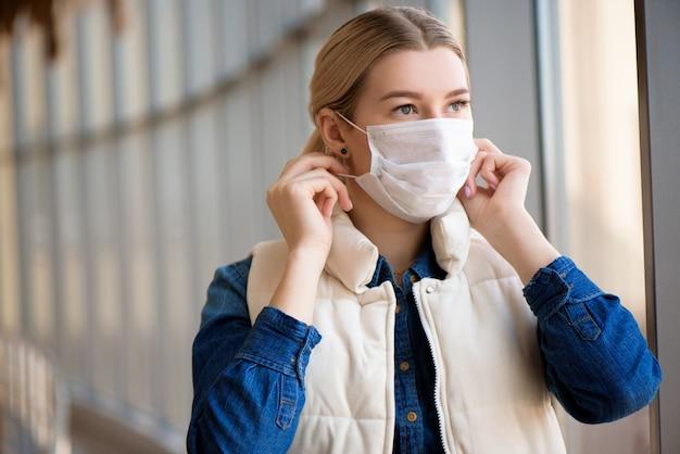 Donna che utilizza la maschera per la protezione nel terminal dell'aeroporto. coronavirus di wuhan e sintomi del virus dell'epidemia