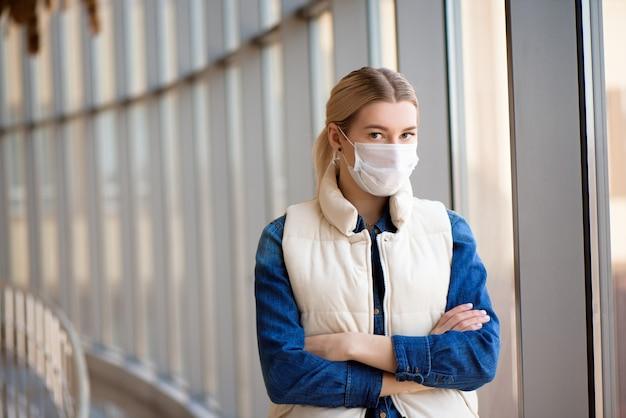 Donna che utilizza la maschera per la protezione pm2.5 nel terminal dell'aeroporto. sintomi di coronavirus e virus dell'epidemia