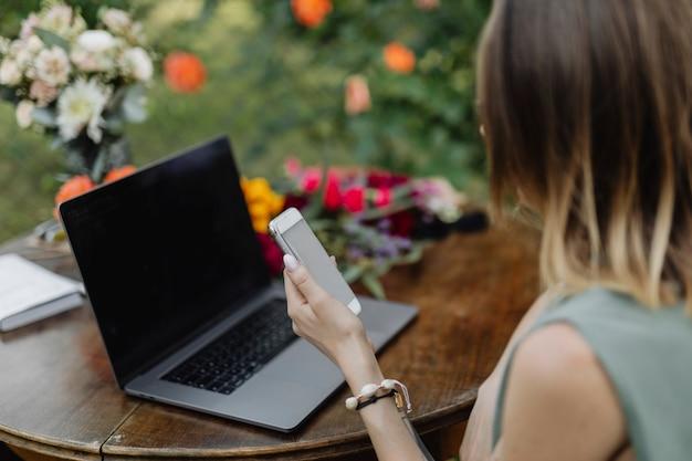 Donna che utilizza un telefono cellulare e un laptop in giardino
