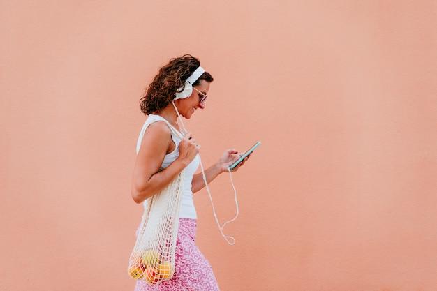 Donna che utilizza il telefono cellulare, ascoltando la musica in cuffia. passeggiando per la città con un sacchetto di cotone con frutta.