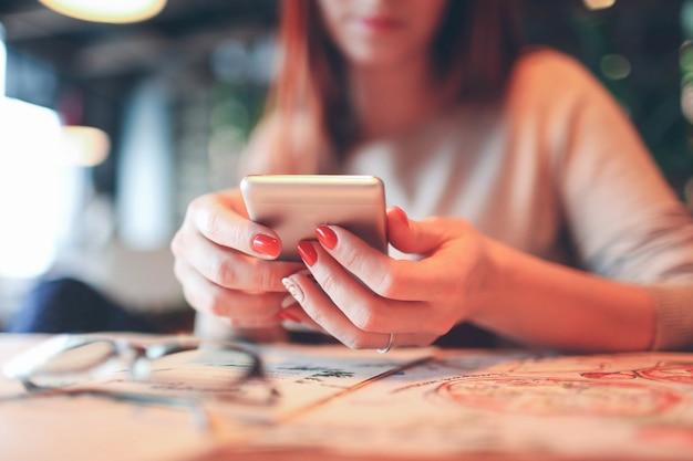 Donna che utilizza un telefono cellulare nel ristorante