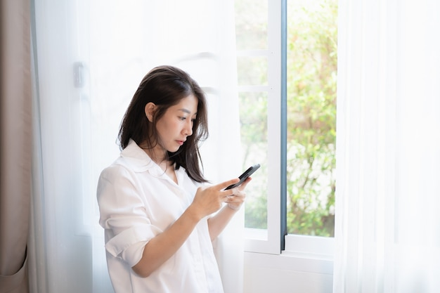 Donna che utilizza il telefono cellulare e in piedi alla finestra in camera da letto