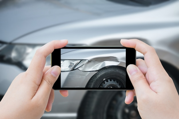 Donna che utilizza smartphone mobile scatta foto incidente d'auto incidente