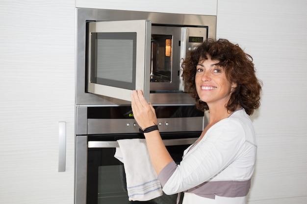 Donna che utilizza forno nella sua cucina alla casa moderna