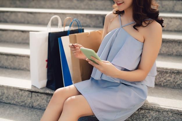 Donna che utilizza il telefono e tiene la carta di credito per effettuare acquisti online mentre è seduta sulle scale all'aperto.