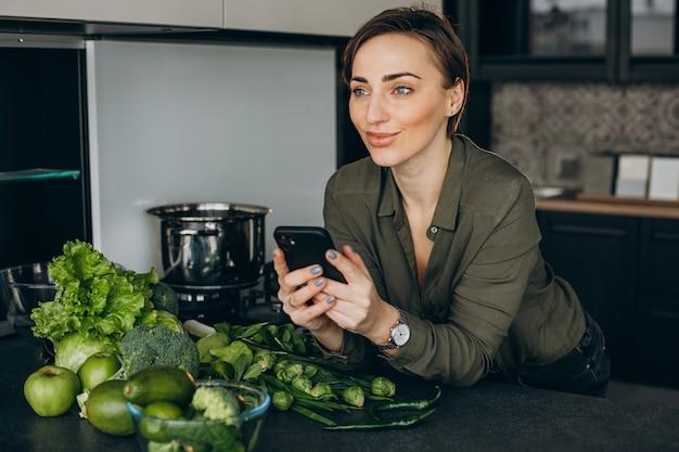 Donna che utilizza il telefono in cucina e cucinare il pasto di verdure verdi