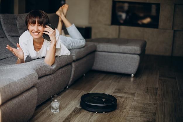 Donna che usa il telefono mentre il robot aspirapolvere pulisce il pavimento