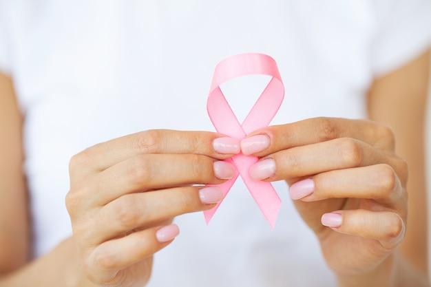 Donna che utilizza il nastro rosa per sostenere la causa del cancro al seno o l'aids.