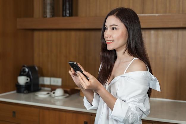 Donna che utilizza smartphone nella stanza della cucina