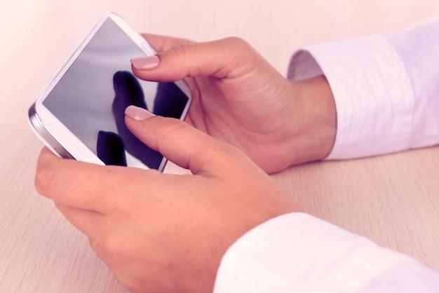 Donna che utilizza smartphone su superficie chiara