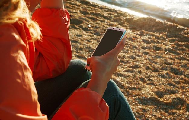 Donna che utilizza uno smartphone seduto sulla spiaggia al tramonto.