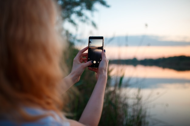 Donna che utilizza smartphone e scattare foto del tramonto colorato sopra il lago.