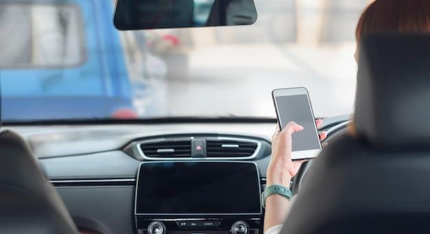 Donna che utilizza smartphone mentre si guida un'auto.