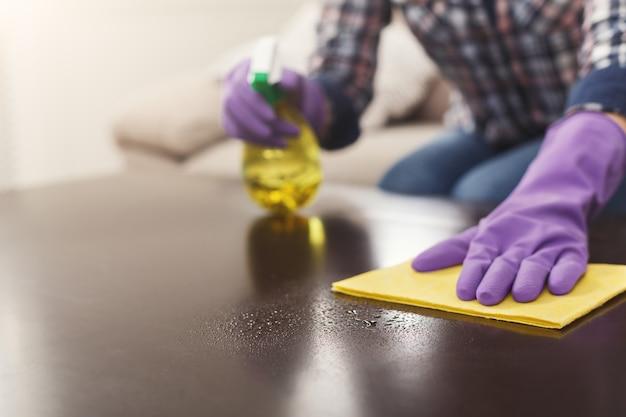 Donna che usa un detergente spray su una superficie di legno