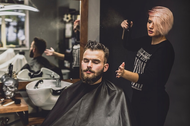 Donna che utilizza spray sull'uomo nel negozio di barbiere