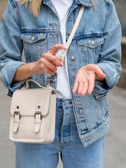 Donna che usando spray con disinfettante per le mani