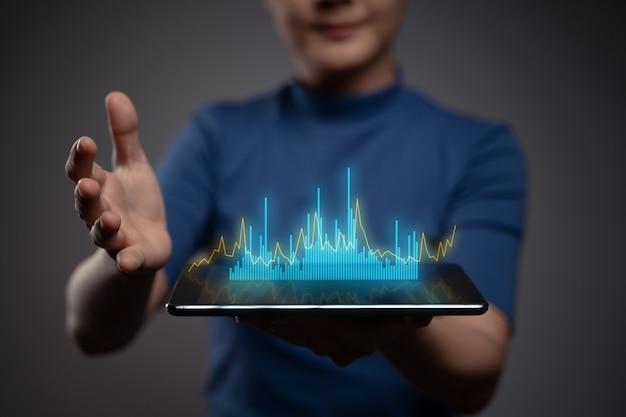 Donna che utilizza tablet pianificazione marketing digitale con effetto ologramma grafico