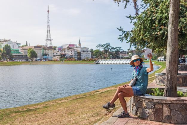 Donna che utilizza lo smart phone della compressa nel lago verde del parco della città nella città del lat del da, vietnam. signora con il cappello vietnamita che prende selfie
