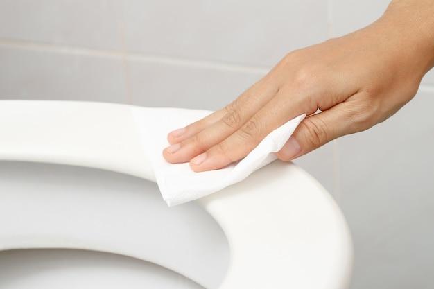 La donna che usa la carta velina pulisce la toilette nel bagno di casa.