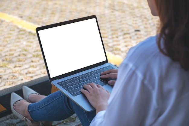 Donna che utilizza e digita sul portatile con schermo bianco vuoto, seduto nel parcheggio all'aperto