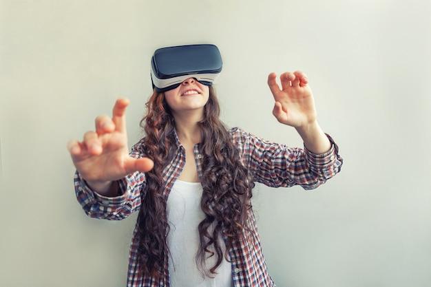 Donna che utilizza la realtà virtuale vr occhiali casco auricolare su sfondo bianco