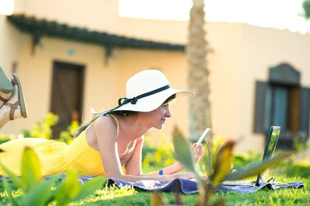 Donna in vacanza sdraiata sul prato di erba verde che lavora su laptop connesso a internet wireless con conversazione sul cellulare nel parco estivo. fare affari e studiare da remoto il concetto.
