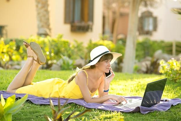 Donna in vacanza sdraiata sul prato di erba verde che lavora su laptop connesso a internet wireless con conversazione sul telefono cellulare nel parco estivo. fare affari e studiare da remoto il concetto.