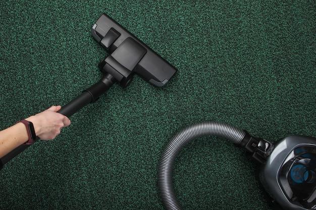 Donna che aspira un tappeto con un aspirapolvere