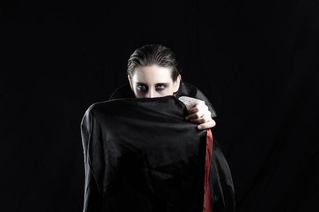 Donna in costume da vampiro per halloween. studio shot di una giovane donna vestita in costume di dracula su sfondo nero