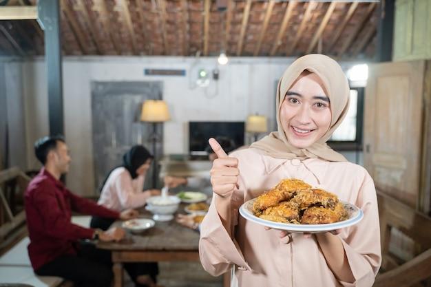 Donna in velo che porta un piatto di pollo fritto con il pollice in alto sullo sfondo i membri della famiglia mangiano...