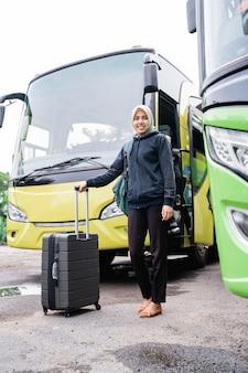 Una donna in velo sorride guardando la telecamera mentre tiene una valigia contro il muro dell'autobus prima di partire
