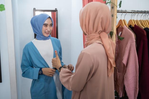 Una donna con il velo si prova dei vestiti in uno spogliatoio davanti allo specchio e la sua amica si compiace...
