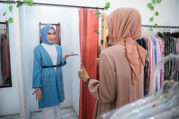 Una donna con il velo si prova dei vestiti in uno spogliatoio davanti allo specchio e viene mostrata alla sua amica