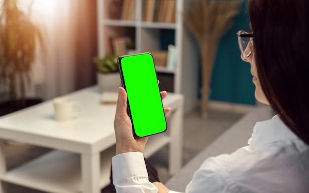 Donna che tiene verticalmente smartphone con schermo verde seduto in appartamento, luce solare attraverso la finestra