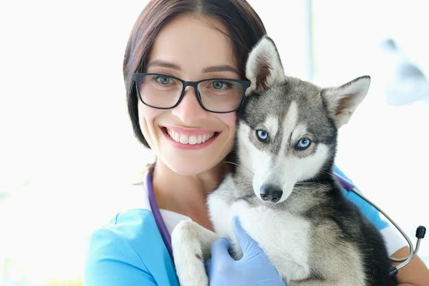 Cane veterinario della tenuta della donna con gli occhi azzurri contro il fondo della clinica dell'animale domestico