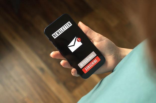 Donna che visualizza la pagina di iscrizione alla newsletter sullo schermo del telefono cellulare. unisciti e registrati membro, iscriviti per aggiornare le informazioni foto
