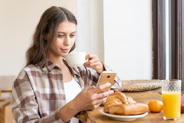 Donna che visualizza i social network utilizzando il cellulare, gustando una sana colazione