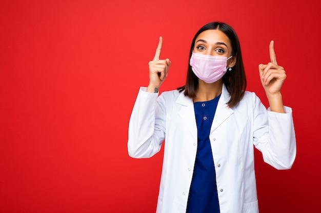 Donna con maschera protettiva contro il virus sul viso contro il coronavirus e camice bianco isolato sullo sfondo e puntando le dita verso l'alto.