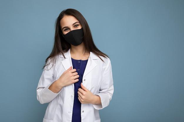 Donna in maschera protettiva contro il virus sul viso contro il coronavirus e camice bianco medico isolato su sfondo blu. copia spazio