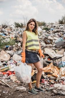 La donna volontaria aiuta a pulire il campo di immondizia di plastica. cespugli e cielo sullo sfondo. giornata della terra ed ecologia.