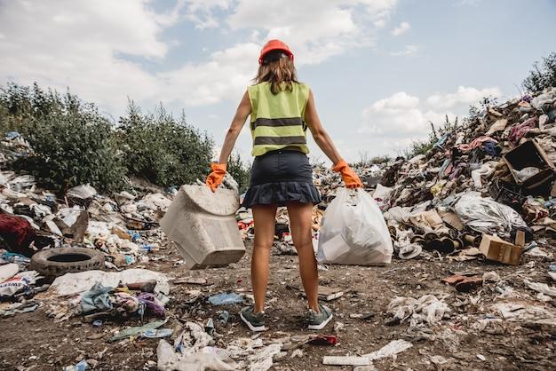 La donna volontaria aiuta a pulire il campo di immondizia di plastica. giornata della terra ed ecologia.